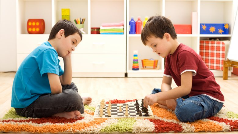 Let me show you a move - kids playing chess sitting on the floor in their room