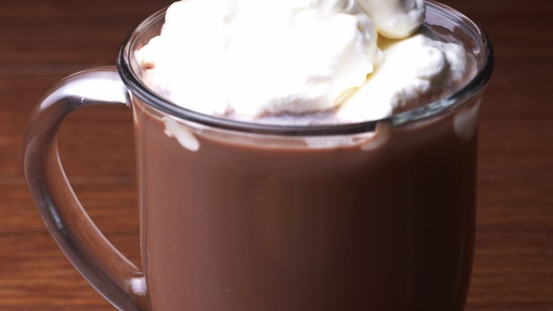 A mug of hot chocolate sits on a table. ** Note: Shallow depth of field